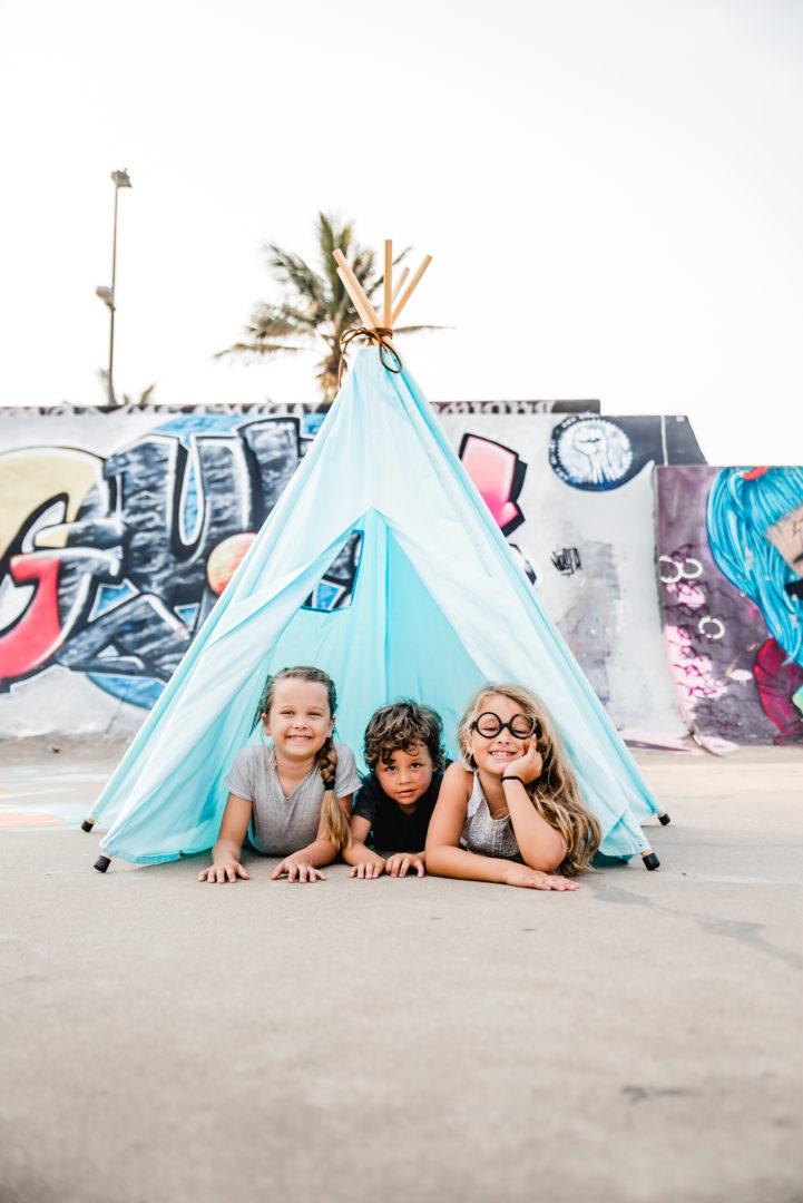 kids inside teepee play tent at skatepark graffiti