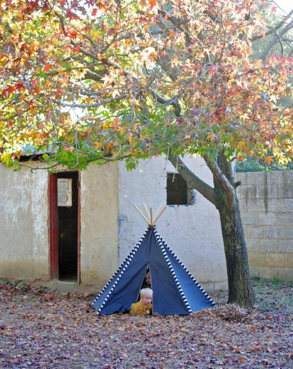 Dark grey teepee play tent under autumn tree